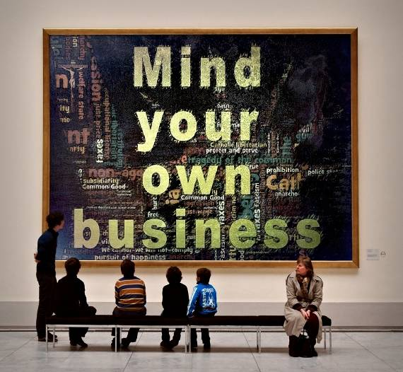 Graphic showing a museum exhibit that reads MInd your own business.- Catholic Libertarian